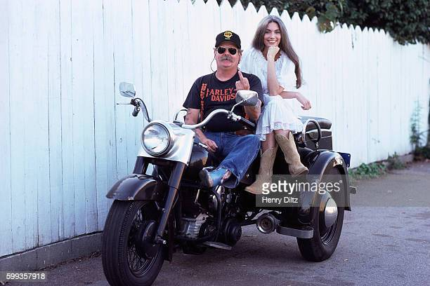 Countryfolk singer Emmylou Harris sits on the back of a threewheeled motorcycle with manager Phil Kaufman who is flipping the bird