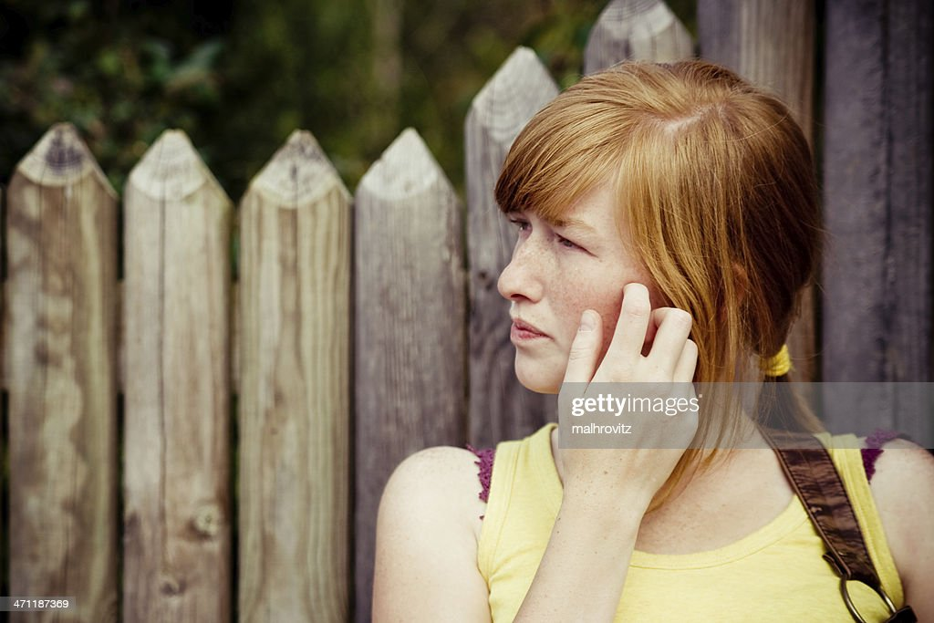 Countryside girl scratching her face : Stock Photo