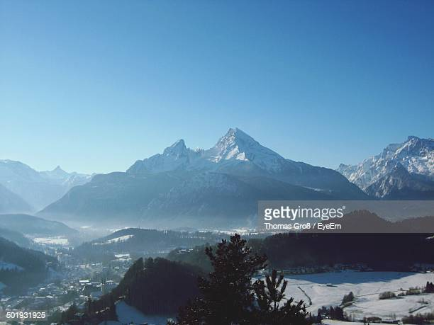 countryside landscape against mountains and clear blue sky - watzmann massif stock photos and pictures