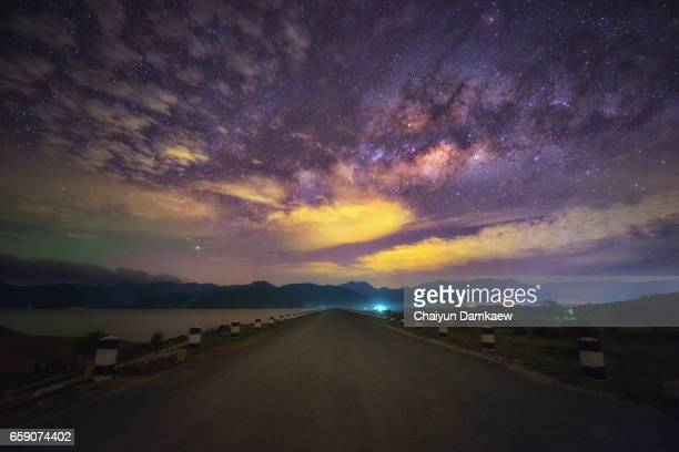 Countryside road in perspective which leads to the milky way