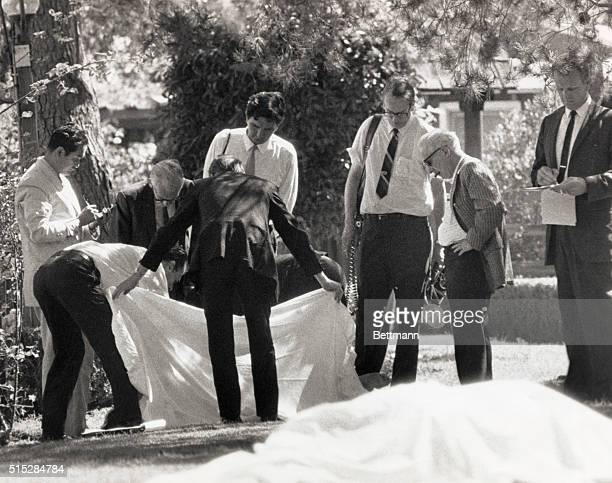 County Coroner Thomas Nogouchi takes notes as assistants hold sheet which covered one body as the other of the two bodies found on the lawn of the...