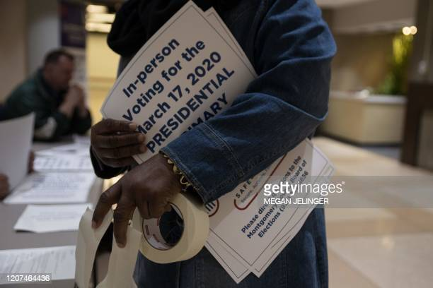 County election workers hand out election delayed signs to put up at polling stations in Dayton Ohio on March 17 2020 after the primaries were...