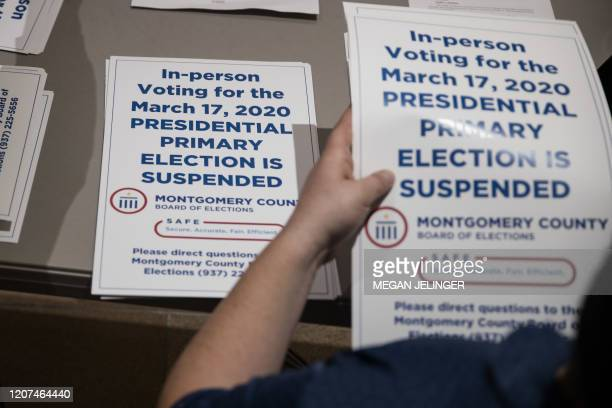 TOPSHOT County election workers hand out election delayed signs to put up at polling stations in Dayton Ohio on March 17 2020 after the primaries...
