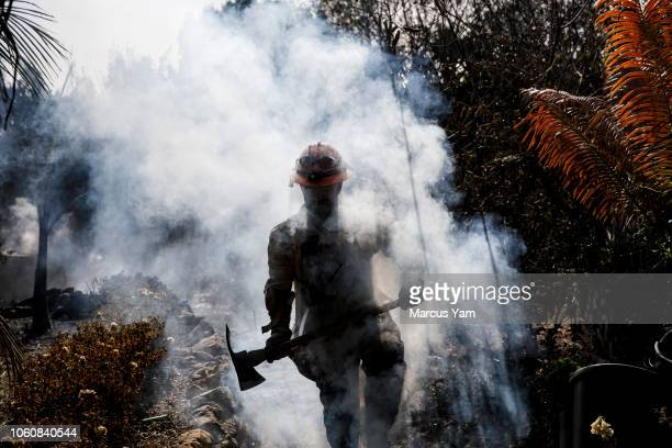 County firefighter Battalion 13 Captain Victor Correa helps put out hotspot in a neighborhood razed by the Woolsey fire on Harvester road November 12...