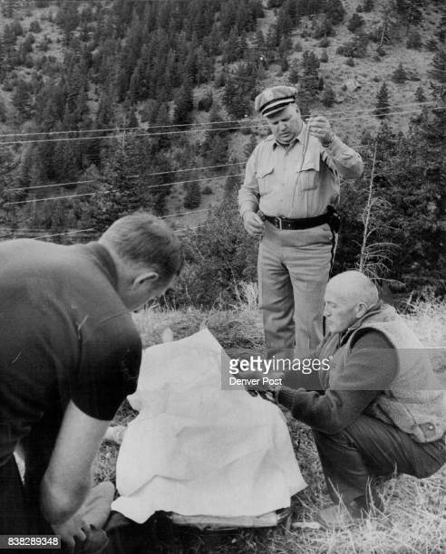 County Officials Check Clues Near Body Dr Freeman D Fowler right Clear Creek County deputy coroner examines a ring while Undersheriff Jim Miller...