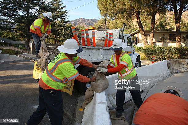 County workers add sand bags to concrete Krails to divert mud flows around homes in advance of the first rain storm since before the massive Station...