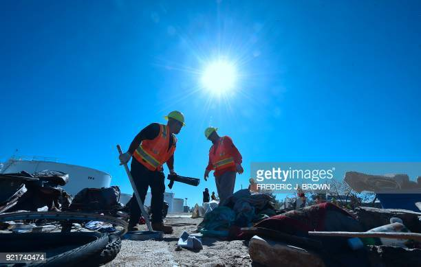 County workers help clear tents and belongings at the homeless encampment beside the Santa Ana River in Anaheim California on February 20 2018...