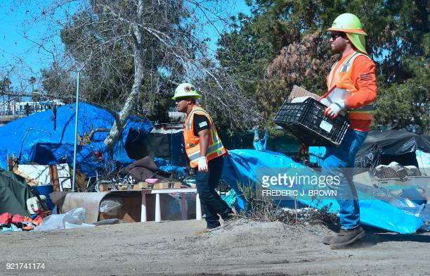 County workers help clear tents and belongings at the homeless encampment beside the Santa Ana River on February 20 2018 Officials in Orange County...