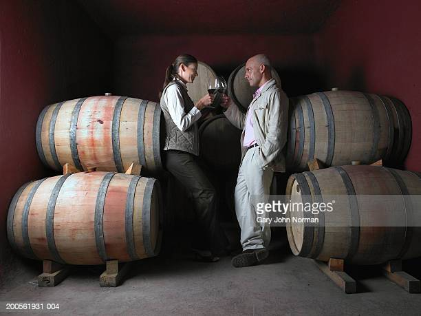 Coupel toasting wine by barrels in wine cellar