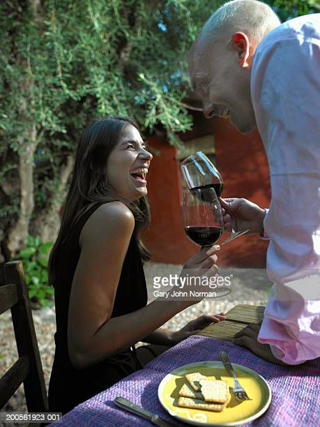 Coupel toasting wine outdoors, smiling