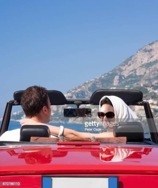 coupl in red car with roof down - pañuelo de cabeza fotografías e imágenes de stock
