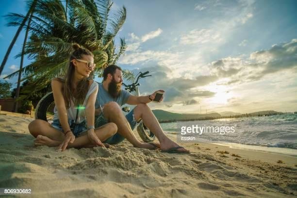 バイクで海に夕日を見ているカップル - 髭の男とビーチの上に座って彼のハンサムなガール フレンドを突いた