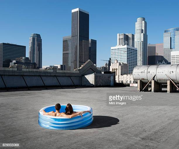 A couple, a man and woman sitting in a small inflatable water pool on a city rooftop, cooling down.