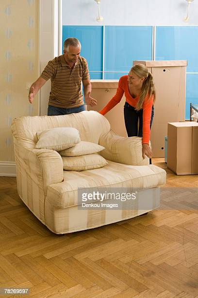 Couple adjusting an armchair and smiling