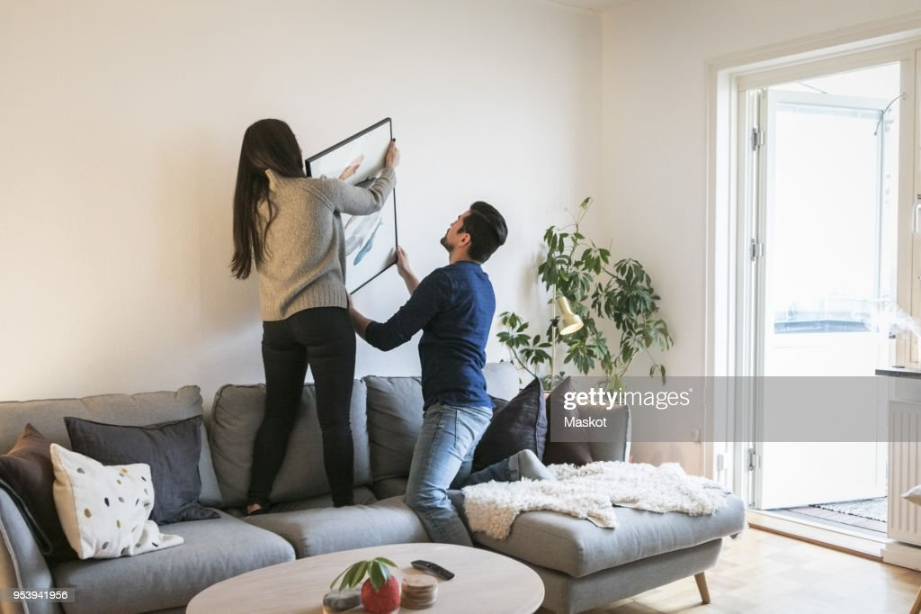 Couple adjusting painting on wall while leaning on sofa at home : Stock Photo