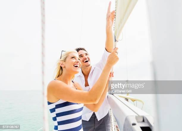 Couple adjusting rigging on sailboat