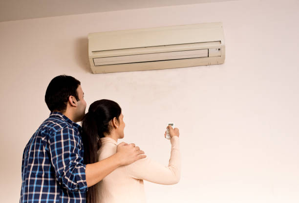 couple adjusting the temperature of air conditioner using remote control - air conditioner stock pictures, royalty-free photos & images