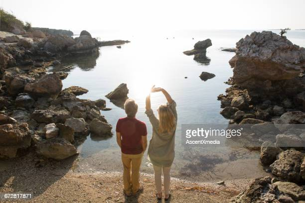 Couple admire the sun on private, rocky beach