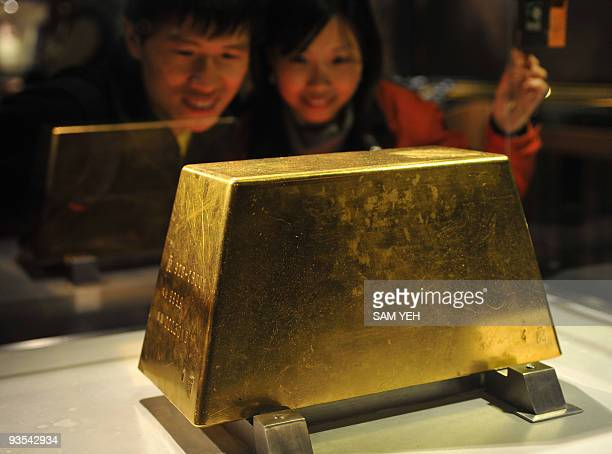 A couple admire the world's largest solid gold brick weighing 220kg at the Jinguashi Gold Museum in Ruifang Taipei county on December 2 2009 Hong...