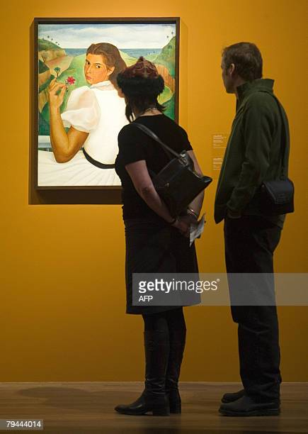 A couple admires a piece called Retrato de Mary by Jorge Arche during The Cuba Art and History from 1868 to Today exhibition 31 January 2008 at the...