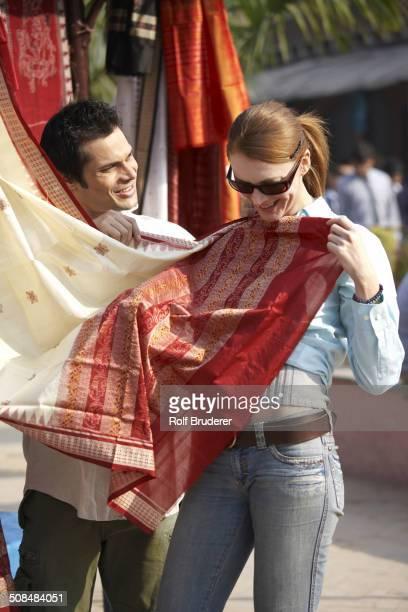 Couple admiring fabrics at outdoor market