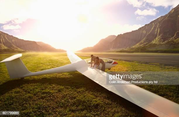 couple admiring glider airplane on remote runway - glider - fotografias e filmes do acervo