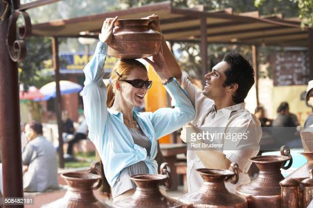couple admiring pottery at outdoor market - incidental people stock pictures, royalty-free photos & images