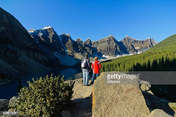 couple admiring the natural beauty of moraine lake - ogphoto stock photos and pictures