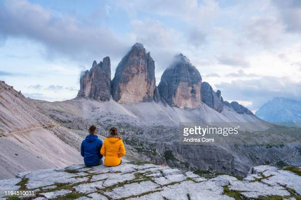 couple admiring the three peaks of lavaredo, italy - トレチーメディラバレード ストックフォトと画像