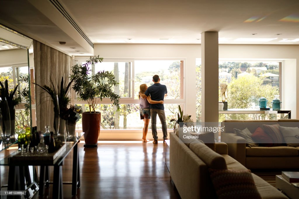Couple admiring the view from the living room of their house. : Stock Photo