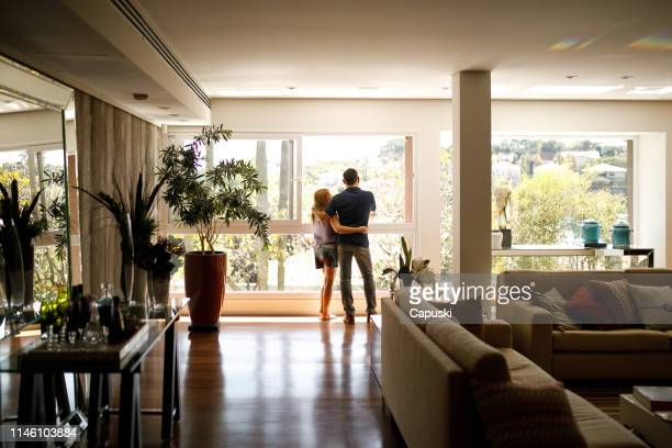 couple admiring the view from the living room of their house. - at home imagens e fotografias de stock