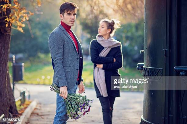 Couple after conflict is standing confused in the public park