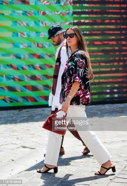 Couple Alice Barbier wearing Prada shirt white pants and JeanSebastien Roques seen wearing vest bordeaux pants bucket hat white button shirt outside...