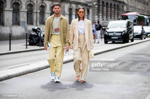 Couple Alice Barbier wearing white dress green white striped sandals green Kenzo bag and JeanSebastien Roques seen wearing mini Jaquemus bag beige...