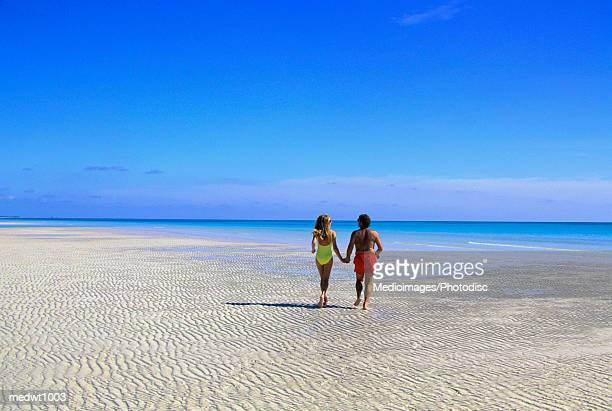 couple alone on beach at lucayan national park, grand bahama island, bahamas - lucayan national park stock photos and pictures