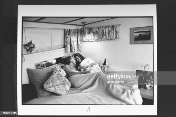 Couple Amie Breed David Strohm enjoy intimate moment drinking champagne in bed on cruise boat getaway w Bayside Boat Breakfast on harbor of San...