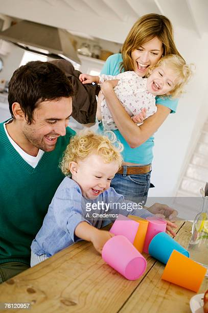 Couple and 2 children playing in kitchen