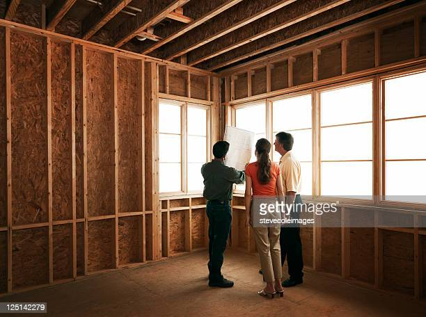 Couple and Builder at Construction Site