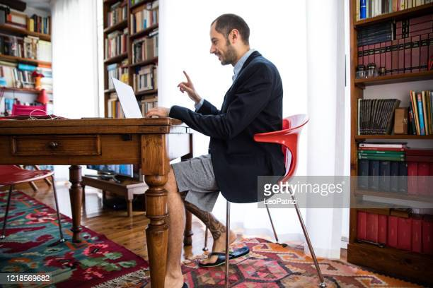 couple and business partner workin at home together in video conference during covid-19 lockdown - shorts stock pictures, royalty-free photos & images