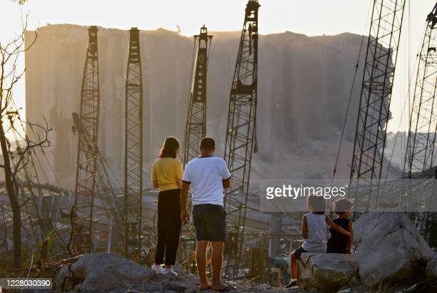 Couple and children contemplate the damage in front of the grain silo at the port of Beirut on August 13 more than a week after a massive blast...
