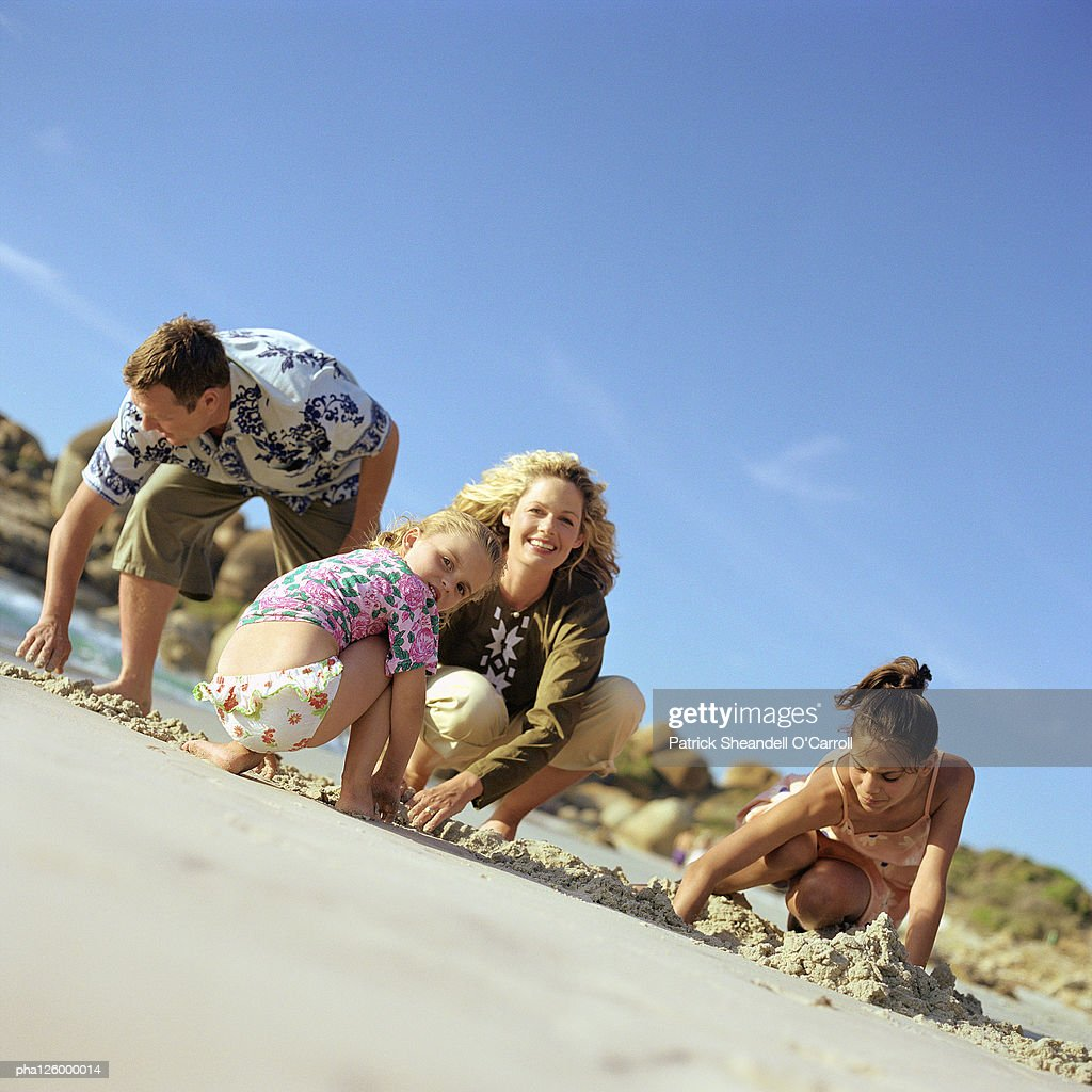 Couple and children digging in sand, portrait : Stockfoto