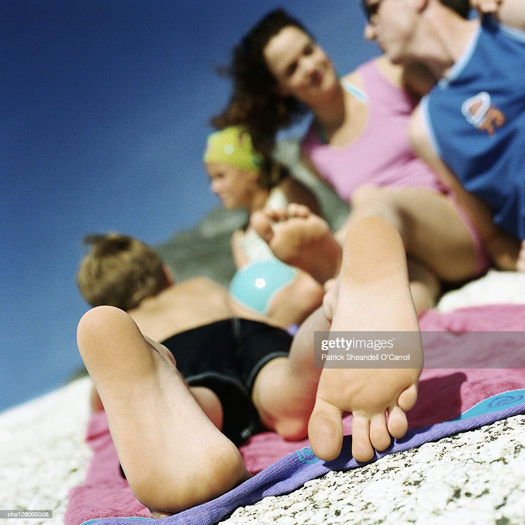 Couple and children lying on beach, focus on child's feet : Stockfoto