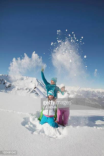 Couple and daughter in ski wear, throwing snow in air