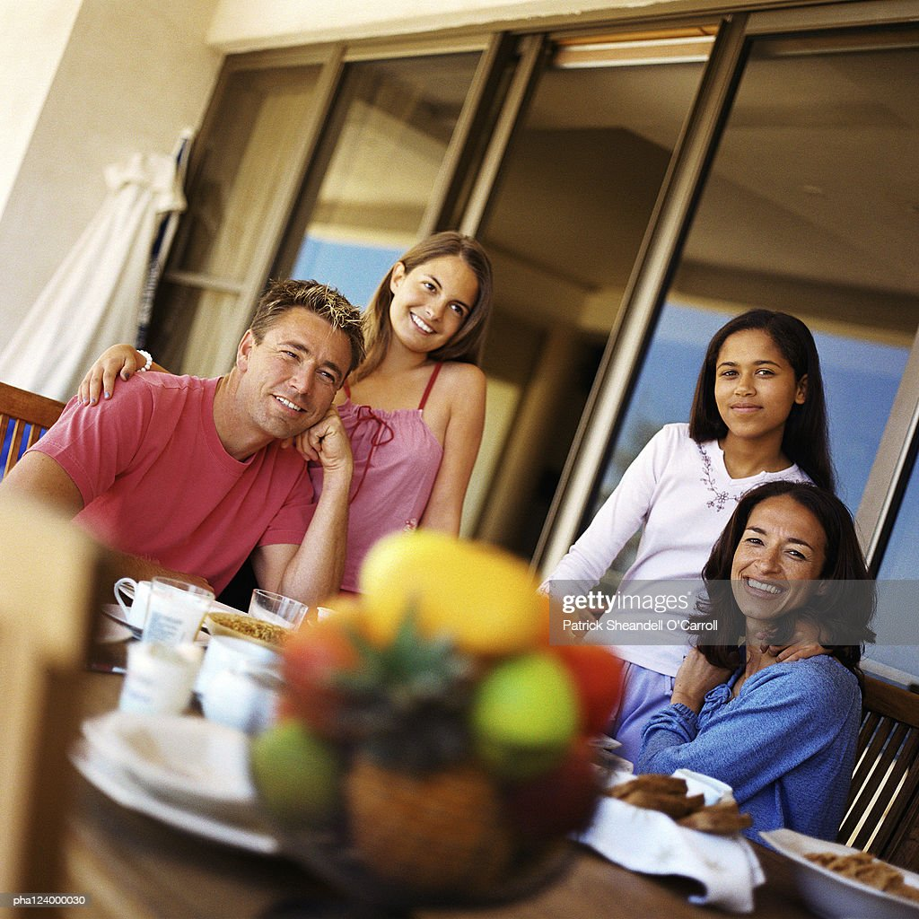 Couple and daughters at table, smiling : Stockfoto