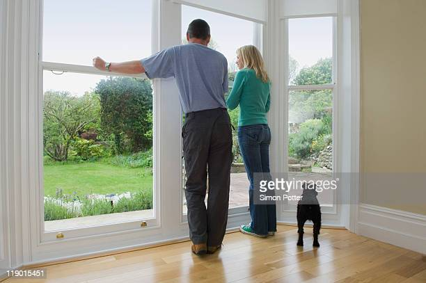 Couple and dog admiring new home