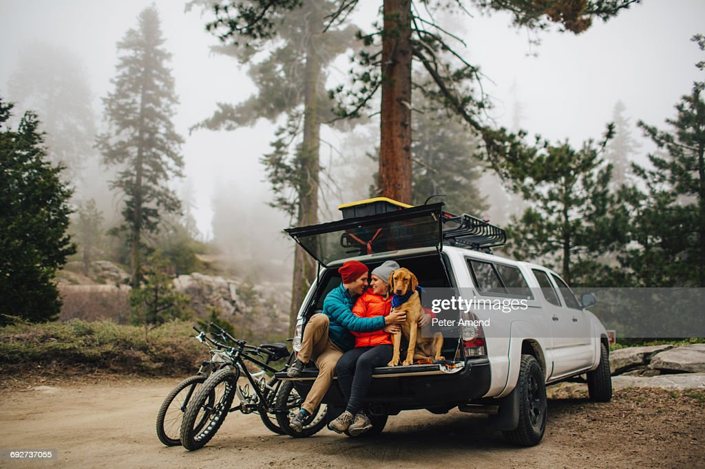 Couple and dog sitting on tailgate of jeep wagon, Sequoia National Park, California, USA : Stock-Foto
