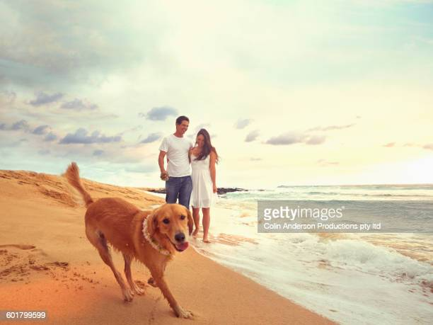 Couple and dog walking on beach