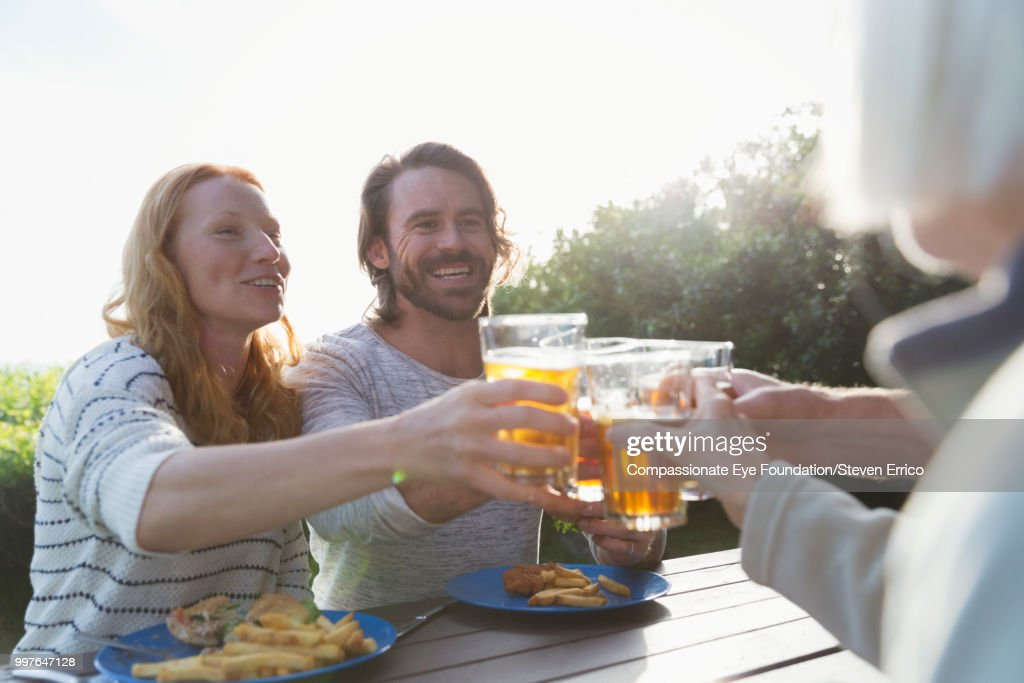 Couple and family toasting with beer glasses at campsite picnic table : Stock Photo