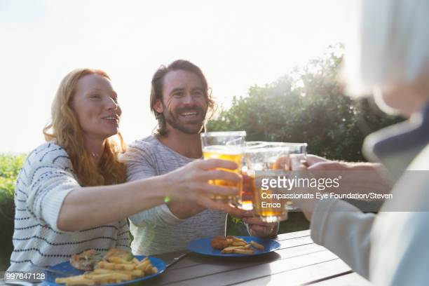 Couple and family toasting with beer glasses at campsite picnic table