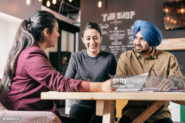couple and financial advisor - sikh stock pictures, royalty-free photos & images
